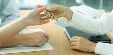Professional woman handing keys to young couple